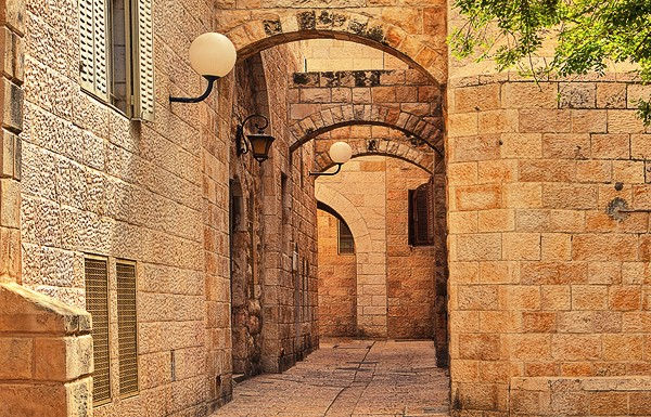 Narrown cobbled street among traditional stoned houses of jewish quarter at old historic part of jerusalem, Israel.